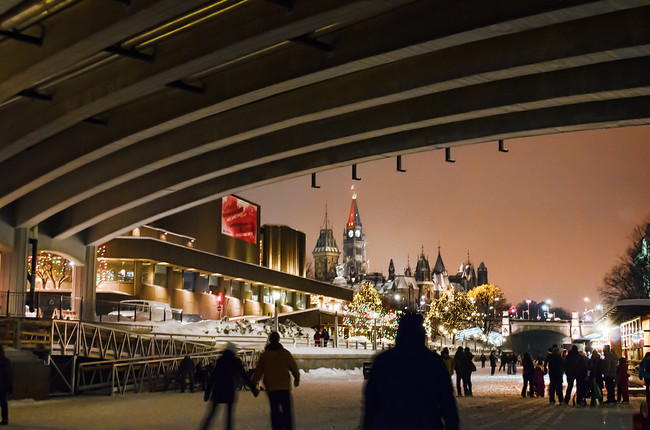 Ice Skating on the Rideau Canal at Dusk Under a Bridge in Ottawa