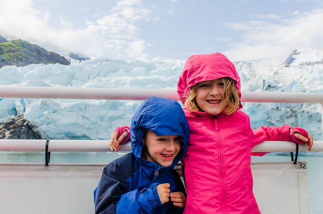 children on a boat next to a glacier