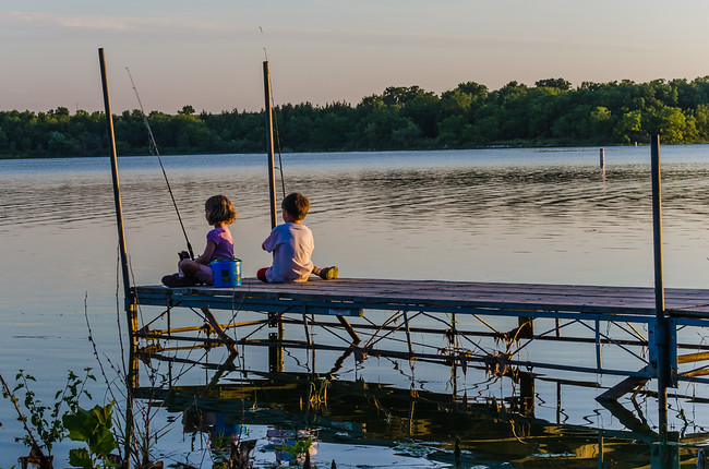 Two kids fishing off a pier in Iowa