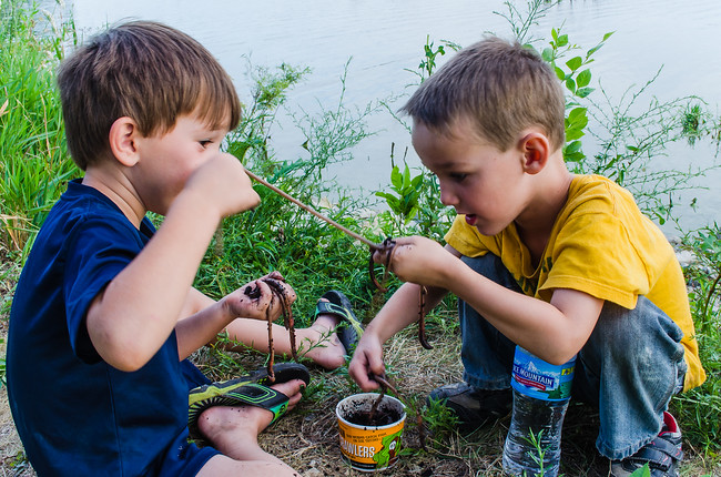 Boys playing with worms by the lake