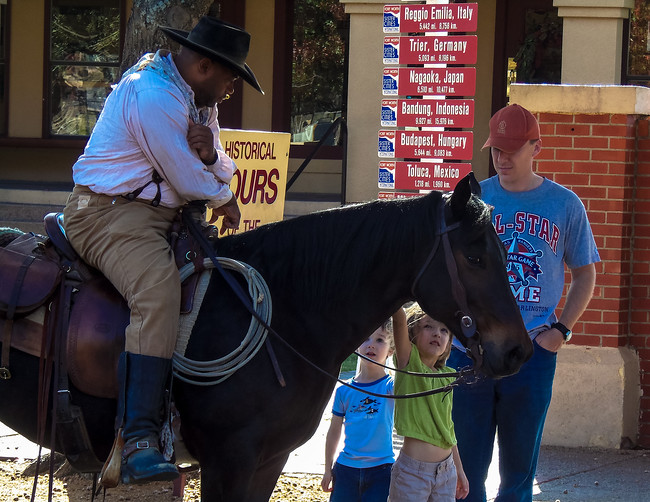 cattle drover talking to children in the fort worth stockyards